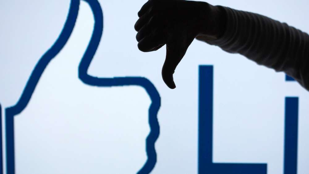 "FILE - ILLUSTRATION - A woman makes the &#39thumbs down&#39 sign with her fist and thumb in front of an enlarged &#39Like&#39 symbol of the social netweorking site Facebook in Schwerin, Germany, 04 April 2013 (STAGED PICTURE). Photo: Jens Buettner/dpa (zu dpa ""Zuckerberg: Facebook arbeitet an ""Gefällt mir nicht""-Knopf"" vom 15.09.2015) +++(c) dpa - Bildfunk+++"