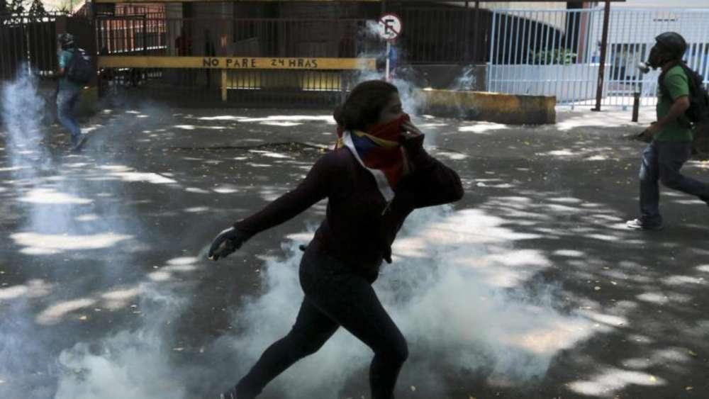 Ein Demonstrant schmeißt einen Tränengaskanister auf Polizisten während der Proteste in Caracas