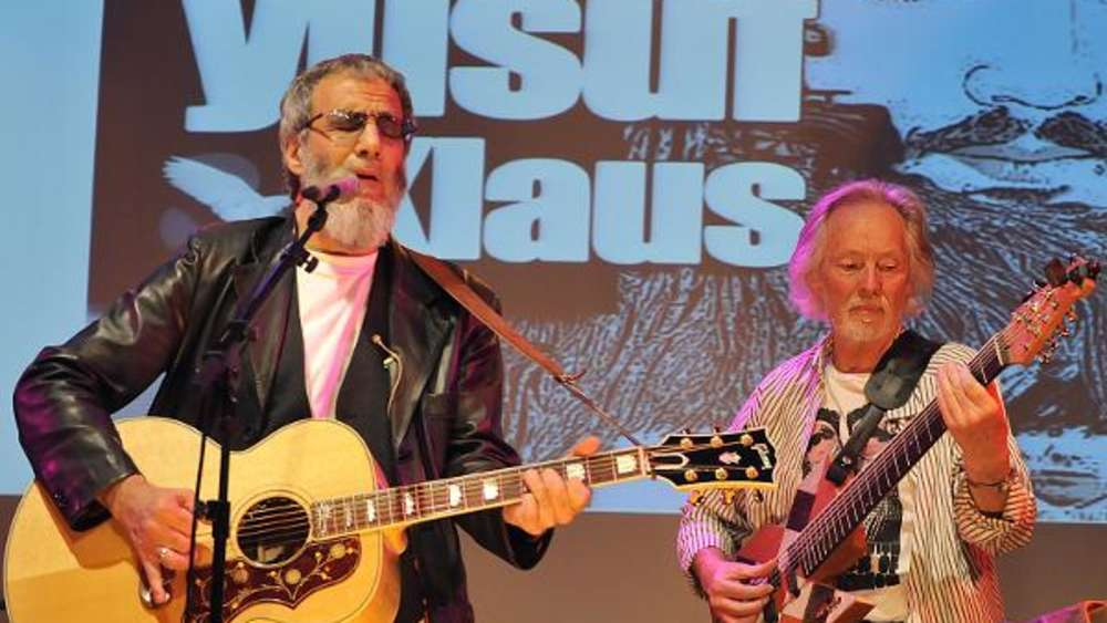 """Wir mögen uns"": Yusuf Islam (Cat Stevens, li.) und Klaus Voormann spielten George Harrisons Song ""All Things Must Pass"". Der Beatle blickt im Hintergrund vom Cover der LP ""Revolver"", das Voormann 1966 entworfen hat."