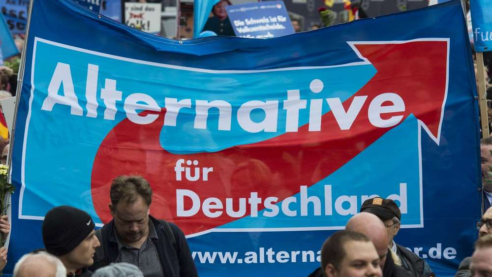 Supporters of the right-wing populist Alternative for Germany (AfD) party display an AfD banner during a demonstration by AfD supporters in Berlin on November 7, 2015. Thousands of protesters marched through the streets of the capital asking for the ouster of German Chancellor Angela Merkel and a curb on the number of asylum-seekers entering Germany. AFP PHOTO / JOHN MACDOUGALL