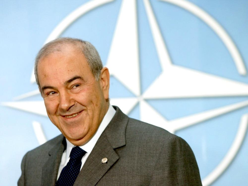 epa000307723 Iraqi Prime Minister Iyad Allawi smiles as he passes by a logo, Friday 05 November 2004, during a visit to NATO headquarters in Brussels. Allawi is also due to attend a meeting at the European Summit held in Brussels. Foto: Herwig Vergult dpa