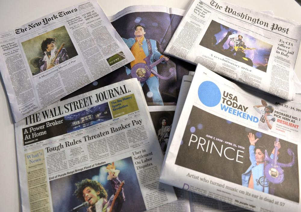 A setup shows a collection of US papers and their coverage of Prince in Washington, DC on April 22, 2016, the day after this death.The groundswell of grief over Prince's death kept flowing as fans prayed an autopsy would eventually reveal what killed one of the music world's most beloved and respected figures. / AFP PHOTO / ANDREW CABALLERO-REYNOLDS