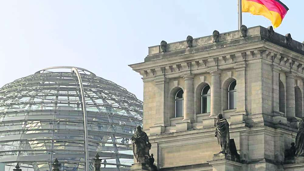 German flag flutters half-mast on top of the Reichstag building, the seat of the German lower house of parliament Bundestag in Berlin