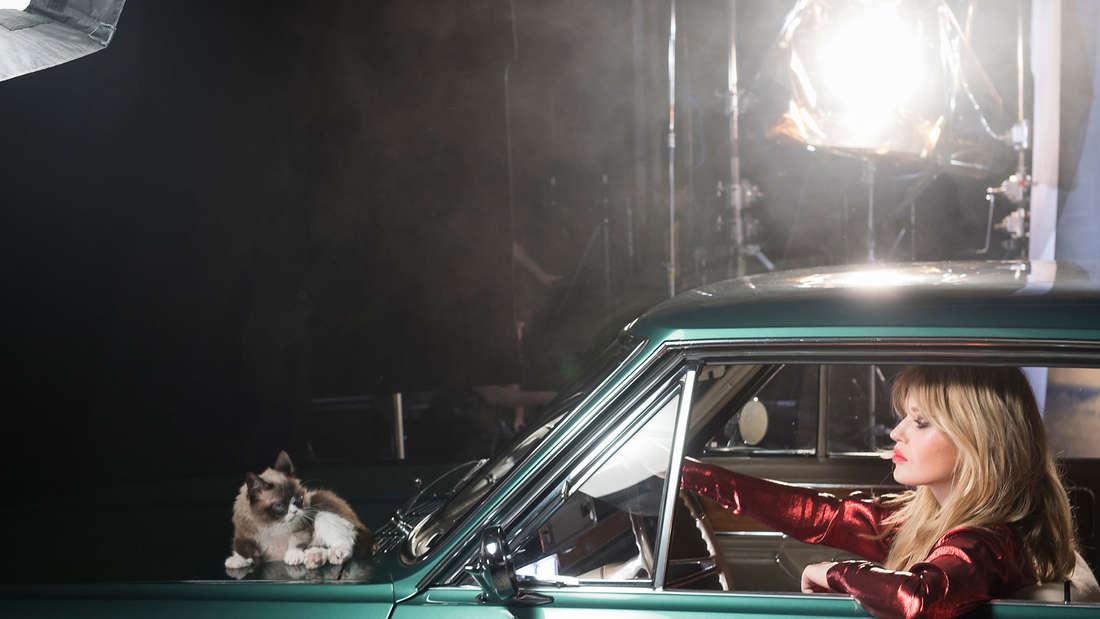 """""""Grumpy Cat"""" lümmelt auf der Motorhaube. Die Katze hatte beim Shooting für denOpel-Kalender 2017 schlechte Laune. Daran konnte auch Georgia May Jagger nichts ändern."""