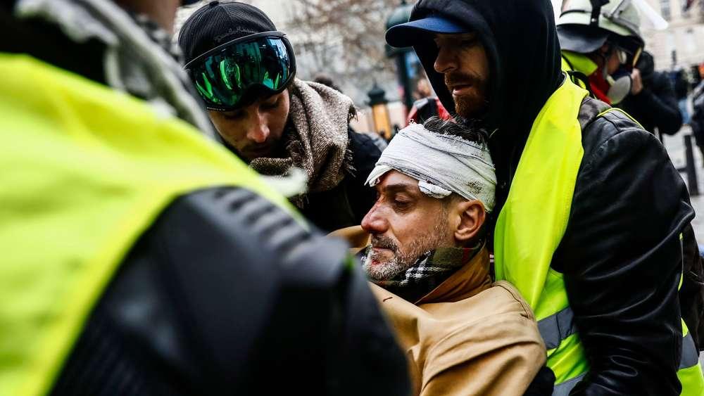 Demonstranten helfen einem verletzten Mann in Paris.