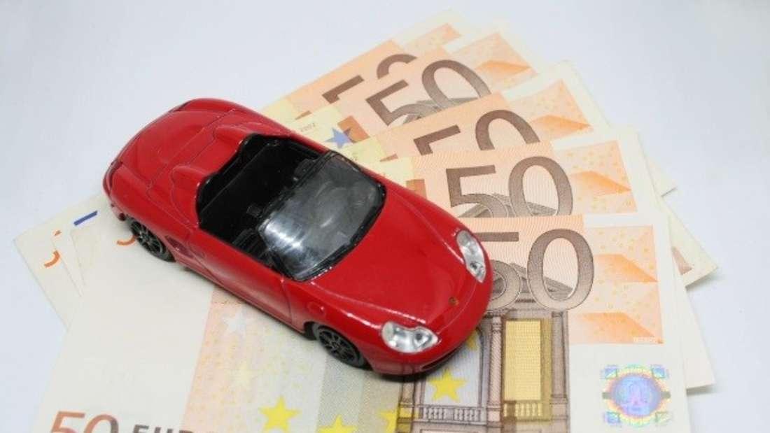 Roter Porsche auf einem Fächer aus Geldscheinen.