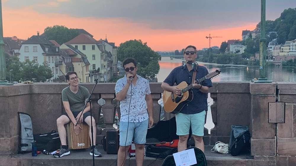 Drei junge Männer stehen auf einer Brücke und machen Musik.