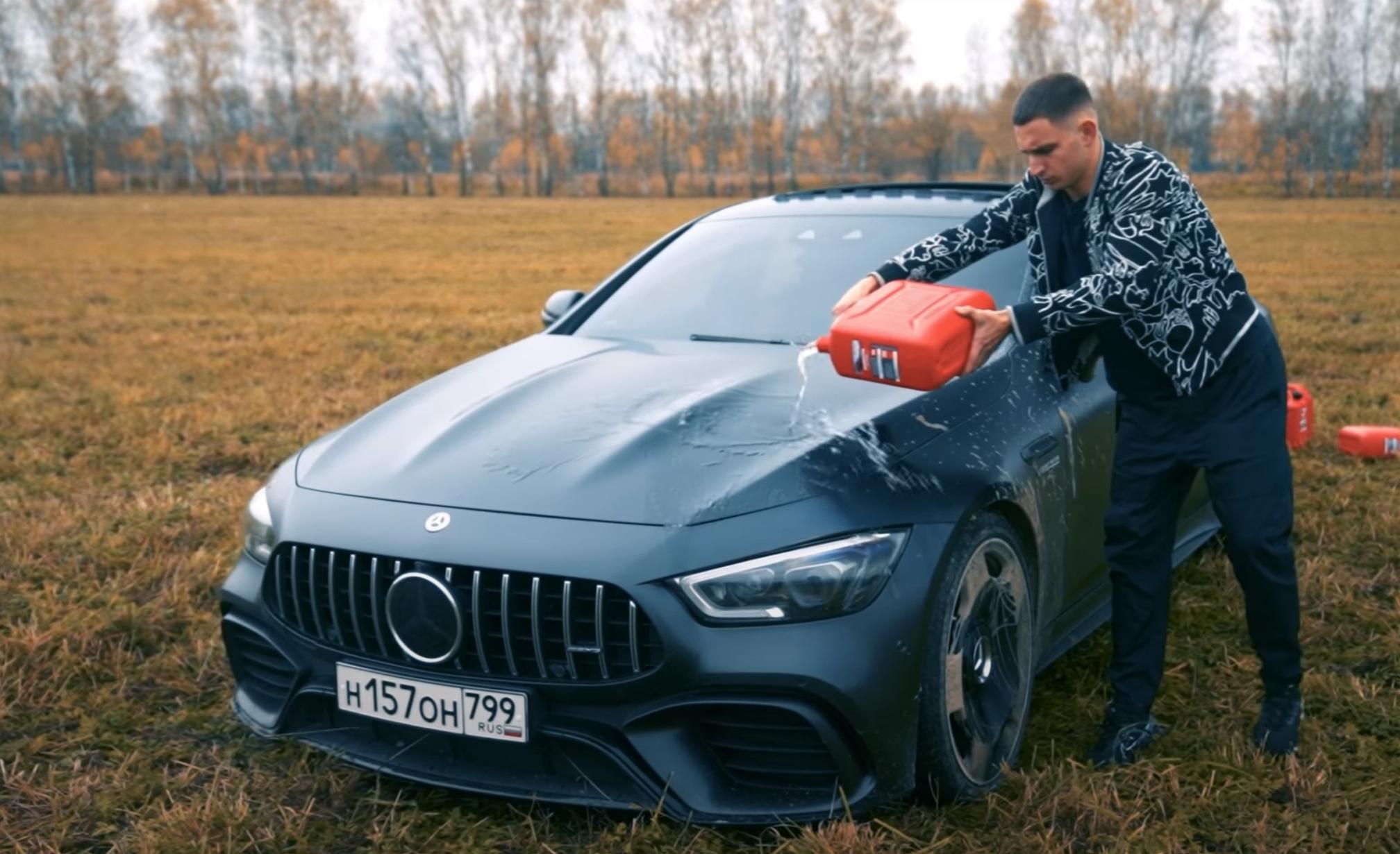 Der Influencer Mikail Litvin übergießt seinen Mercedes-AMG GT 63s Viertürer mit Benzin.
