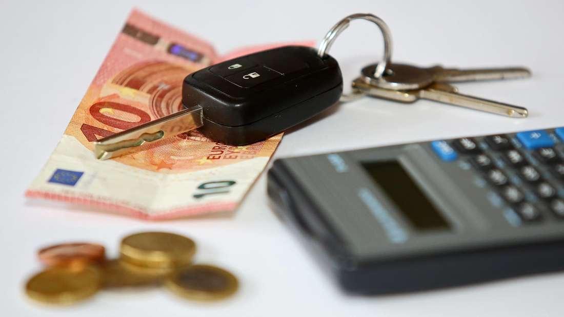 Symbolbild für Kfz-Versicherung mit einem Autoschlüssel, Taschenrechner und Bargeld.
